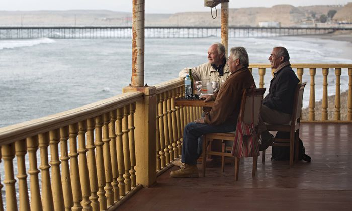Three male friends enjoy a drink and good conversation on colonial style balcony overlooking the oce