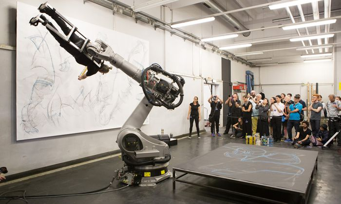 """Hier dient der Maler als Pinsel: Der in Belgrad geborene Künstler Dragan Ilić lässt sich in der Performance """"Roboaction(s)"""" an einem Roboter namens Kuka fixieren, der ihn über die Leinwand bewegt."""