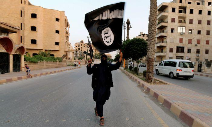 Symbolbild: Kämpfer hält die IS-Flagge in der Stadt Raqqa