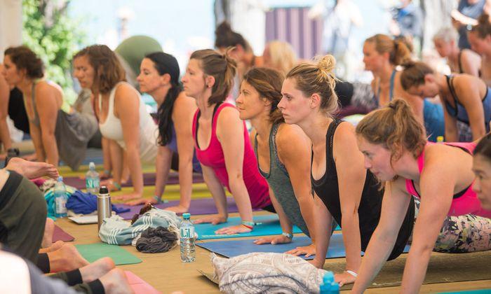 Yoga im Zelt am Wörthersee. Dicht an dicht liegen die Matten, erstaunlicherweise stört es nicht.