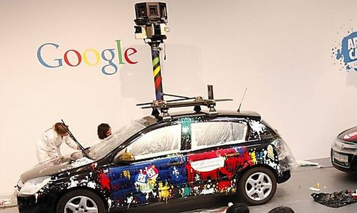 Visitors walk past painted cars with mounted cameras used for Google street view at the CeBIT compute