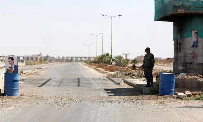 A Syrian soldier stands guard at the Nasib border crossing with Jordan in Deraa