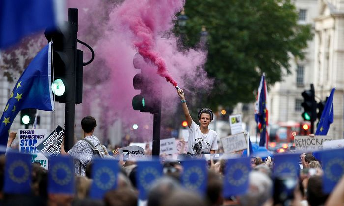 An anti-Brexit protestor releases colored smoke, outside the Houses of Parliament in London