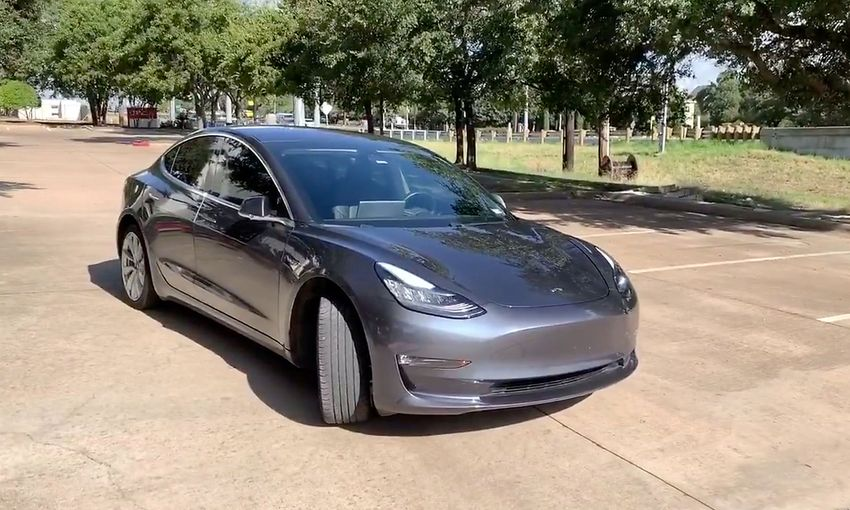 A Tesla 3 model is remotely driven with the company's phone app in Austin, Texas