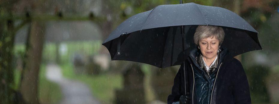 Theresa May kämpft gegen Regen und Gewitter an. In Großbritannien formiert sich immer mehr politischer Widerstand gegen den geplanten Brexit-Deal der Regierungschefin. / Bild: (c) APA/AFP/DANIEL LEAL-OLIVAS (DANIEL LEAL-OLIVAS)